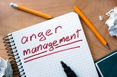 stock photo of anger  - Note with words  anger management  on a wooden background - JPG