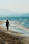 picture of stroll  - Woman strolling on sandy beach of Crete shore - JPG