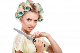 stock photo of shoulder-blade  - Cheerful woman with curlers is holding knife and leaning it on her shoulder - JPG