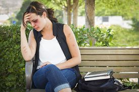 stock photo of bruises  - Sad Bruised and Battered Young Woman Sitting on Bench Outside at a Park - JPG