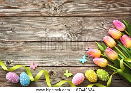 poster of Easter background with colorful eggs, spring tulips and ribbon. Top view with copy space