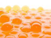 Un montón de bolas semitransparentes de color naranja sobre fondo blanco.