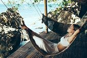 Woman relaxing in the hammock on tropical beach, hot sunny day poster