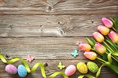 Easter background with colorful eggs, spring tulips and ribbon. Top view with copy space poster