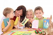 mother and children making Christmas cards /all cards are made by mother and children/