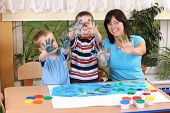 image of 6 year old  - teacher two preschoolers and fingerpainting  - JPG