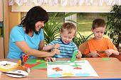 Profesor y dos niños en edad preescolar hacer alguna decoración