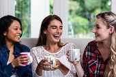 Close-up of cheerful female friends with coffee cup sitting on sofa at home poster