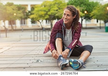 poster of Mature fitness woman tie shoelaces on road. Cheerful runner sitting on floor on city streets with mo
