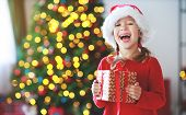 Happy Child Girl With Christmas Gifts Near Christmas Tree In Morning poster