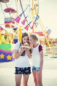 Two teen girls making a silly face while eating a funnel cake at an amusement park ride. Sticking ou poster
