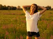 Happy  and serene behavior woman  outdoor. Young cheerful girl is on nature over the spring field. H poster