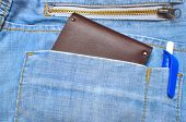 wallet halfway out from a jeans back pocket