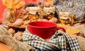 Mug Of Tea Surrounded By Scarf Red Background With Fallen Maple Leaves And Walnuts. Mug Cozy Aromati poster
