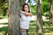 beautiful young woman in park playing peekaboo