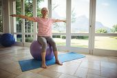 Senior woman performing stretching exercise on fitness ball at home poster