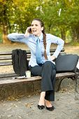 frustrate businesswoman sitting in bench in park and talking on phone