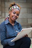 stock photo of academia  - African American college student or office secretary PA taking notes - JPG