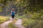 young woman enjoying in a healthy lifestyle while jogging along a country road, exercise and fitness poster
