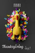 a funny rubber plucked turkey on a pile of confetti, placed on a dark green rustic surface, and the  poster