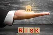 Miniature Wooden House And The Inscription  Risk  . Buying A House, Apartment And Financial Risks. poster