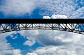 Bridge in the blue sky over white clouds