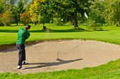 Male golf player pitching off golf ball from the sand bunker, wonderful landscape in background.