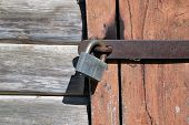 Padlock On The Door Of The Old Log Structure. The Wooden Door Is Closed With A Metal Strip And A Loc poster