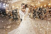 Gorgeous Bride And Stylish Groom Dancing Under Golden Confetti At Wedding Reception. Happy Wedding C poster