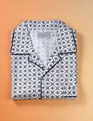 Folded pyjamas top on orange background.