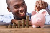 Happy African Man Inserting Coin In Piggybank Near Stack Of Coins poster