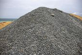 Huge Pile Of Grey Gravel On Coast. Construction Site Material. Big Gravel Heap Outdoor. Construction poster
