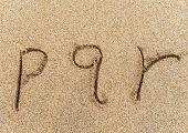 alphabet letters p q r handwritten in sand on beach