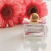 Beautiful perfume bottle with pink flower on the back.  Luxury perfumery background.Floral fragrance poster