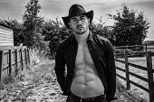 Sexy, Handsome, Cowboy With Open Black Shirt Revealing Pecs And Sixpack Abs Looking At Camera With R poster