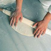 close up shot of a man rolling dough