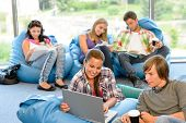 Students sitting on beanbags study room high-school teens happy