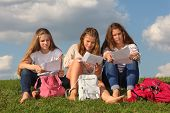 Three girls sit on green grass with bags and read something at background of blue sky.