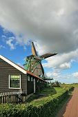 Pastoral landscape in Holland. A windmill and a barn on a green hillock
