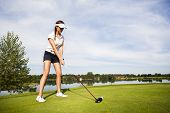 Girl golf player tee-box focusing on golf ball for teeing off.