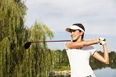 Professional golf player teeing-off with beautiful trees in background, front view.