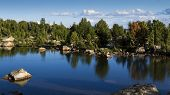 stock photo of beartooth  - A crystal blue lake with surrounding trees and rocks reflecting in it - JPG