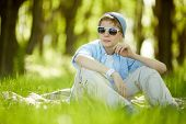 Portrait of cute lad in casual clothes and sunglasses having rest outside