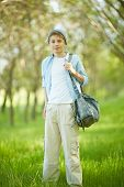 Portrait of cute lad in casual clothes looking at camera outside