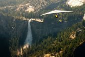 stock photo of hang-gliding  - Aerial view of waterfall and forest in Yosemite National Park with hang glider in foreground viewed from Glacier Point California U - JPG