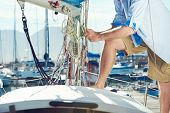 foto of life-boat  - portrait of senior man tying knot and securing a mooring for his hobby yacht sail boat - JPG