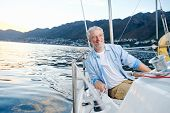 stock photo of sails  - carefree happy sailing man portrait of mature retired man on ocean boat at sunrise - JPG