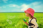image of hair blowing  - Little girl playing with soap bubbles - JPG