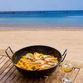 picture of valencia-orange  - Seafood paella with glass of wine in seaside cafe - JPG