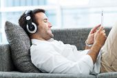 stock photo of couch  - Man on sofa with headphones and digital tablet - JPG